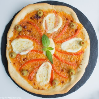 Pizza Margherita di Bufala topped with red peppers and olives
